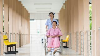 Woman pushing an older woman down a hallway in a wheelchar