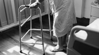 Black and white photo of person standing near hospital bed using a walker